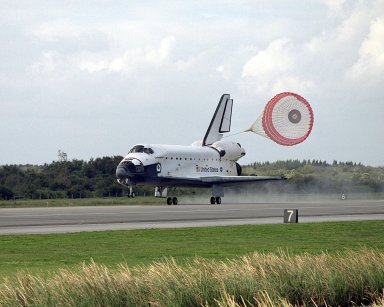 KENNEDY SPACE CENTER, FLA. -- With its drag chute billowing behind, orbiter Endeavour slows for a full touchdown on Runway 15 at the KSC Shuttle Landing Facility, completing mission STS-108. Endeavour carries both the mission crew and the Expedition 3 crew - Commander Frank Culbertson and cosmonauts Vladimir Dezhurov and Mikhail Tyurin - who are returning to Earth after 129 days in space on the International Space Station. After a mission-elapsed time of 11 days, 19 hours and 35 minutes, Endeavour had main gear touchdown at 12:55:10 p.m. EST (17:55:10 GMT). Nose gear touchdown occurred at 12:55:23 p.m. (17:55:23 GMT); wheel stop at 12:56:13 p.m. (17:56:13 GMT). Rollout distance was 8,941 feet. The landing is the 57th at KSC in the history of the program STS-108 was the 12th mission to the Space Station. This mission was the 107th flight in the Shuttle program and the 17th flight for the orbiter