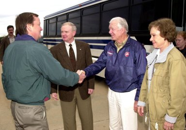 KENNEDY SPACE CENTER, FLA. - Launch Director Mike Leinbach greets former President Jimmy Carter , who is touring Kennedy Space Center with his wife Rosalyn (right). Center Director Roy D. Bridges Jr. stands between Leinbach and Carter