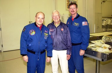 KENNEDY SPACE CENTER, FLA. -- In the Space Station Processing Facility, former President Jimmy Carter (center) pauses for a photo with astronauts Scott Kelly (left) and Joseph Tanner (right). Carter and former First Lady Rosalyn Carter are touring KSC