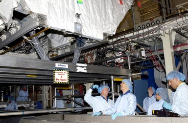 KENNEDY SPACE CENTER, FLA. -- In the Operations and Checkout Building, members of the STS-110 crew check out equipment that will be on their mission. At center are Mission Specialists Jerry L. Ross and Lee Morin. Other crew members (not shown) are Commander Michael J. Bloomfield, Pilot Stephen N. Frick, and Mission Specialists Steven L. Smith, Ellen Ochoa and Rex J. Walheim. Part of the payload on the mission is the Integrated Truss Structure S0. It is the center segment that they will be installing on the International Space Station, part of the 300-foot (91-meter) truss attached to the U.S. Lab. By assembly completion, four more truss segments will attach to either side of the S0 truss. STS-110 is currently scheduled to launch in April 2002