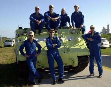 KENNEDY SPACE CENTER, FLA. - After training on the M-113 armored personnel carrier, the STS-109 crew gather for a photo. Seated on top are (left to right) Payload Commander John Grunsfeld, Commander Scott Altman and Mission Specialists Nancie Currie and James Newman; standing below are Pilot Duane Carey and Mission Specialists Richard Linnehan and Michael Massimino. The carrier is part of emergency egress training at the launch pad. The crew is taking part in Terminal Countdown Demonstration Test activities that also include a simulated countdown at the pad. STS-109 is a Hubble Space Telescope Servicing Mission, with goals to replace Solar Array 2 with Solar Array 3, replace the Power Control Unit, remove the Faint Object Camera and install the Advanced Camera for Surveys (ACS), install the Near Infrared Camera and Multi-Object Spectrometer (NICMOS) Cooling System, and install New Outer Blanket Layer insulation. The 11-day mission will require grasping the satellite with a robotic arm in order for the crew to perform the tasks during five spacewalks. Launch of STS-109 aboard Space Shuttle Columbia is scheduled for Feb. 28, 2002