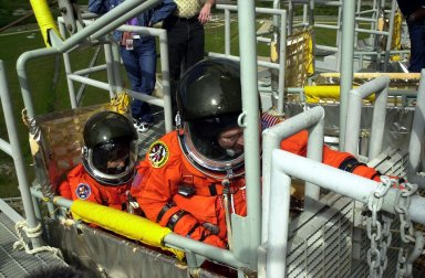 KENNEDY SPACE CENTER, FLA. -- As part of Terminal Countdown Demonstration Test activities, the STS-109 crew practices emergency exit from the Shuttle. Seated in the slidewire basket at the 195-foot level of the Fixed Service Structure are Mission Specialists Nancy Currie (left) and John Grunsfeld (reaching for the release lever). The TCDT also includes a simulated launch countdown. STS-109 is a Hubble Space Telescope Servicing Mission, with goals to replace Solar Array 2 with Solar Array 3, replace the Power Control Unit, remove the Faint Object Camera and install the Advanced Camera for Surveys (ACS), install the Near Infrared Camera and Multi-Object Spectrometer (NICMOS) Cooling System, and install New Outer Blanket Layer insulation. The 11-day mission will require five spacewalks to perform the tasks. Launch of STS-109 aboard Space Shuttle Columbia is scheduled for Feb. 28, 2002