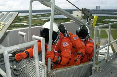 KENNEDY SPACE CENTER, FLA. -- As part of Terminal Countdown Demonstration Test activities, the STS-109 crew practices emergency exit from the Shuttle. Seated in the slidewire basket at the 195-foot level of the Fixed Service Structure are Mission Specialists Richard Linnehan (reaching for the release lever), Michael Massimino and James Newman. The TCDT also includes a simulated launch countdown. STS-109 is a Hubble Space Telescope Servicing Mission, with goals to replace Solar Array 2 with Solar Array 3, replace the Power Control Unit, remove the Faint Object Camera and install the Advanced Camera for Surveys (ACS), install the Near Infrared Camera and Multi-Object Spectrometer (NICMOS) Cooling System, and install New Outer Blanket Layer insulation. The 11-day mission will require five spacewalks to perform the tasks. Launch of STS-109 aboard Space Shuttle Columbia is scheduled for Feb. 28, 2002
