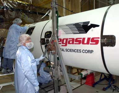 VANDENBERG AFB, CALIF. -- Technicians work on the Pegasus XL rocket, the vehicle that will launch the High Energy Solar Spectroscopic Imager (HESSI). The primary mission of HESSI is to explore the basic physics of particle acceleration and energy release in solar flares. The launch of PegasusXL/HESSI is scheduled for Feb. 5, 2002, from beneath an Orbital Sciences Corp. L-1011 aircraft over the Atlantic Ocean