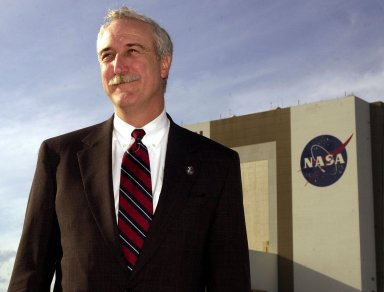 KENNEDY SPACE CENTER, Fla. - The new NASA Administrator Sean O'Keefe poses for the photographer with the Vehicle Assembly Building in the background. The administrator was at KSC on an agencywide familiarization tour of NASA field centers. He was nominated for the position as administrator in November 2001 by President George W. Bush. He was sworn in Dec. 21 as the agency's tenth chief