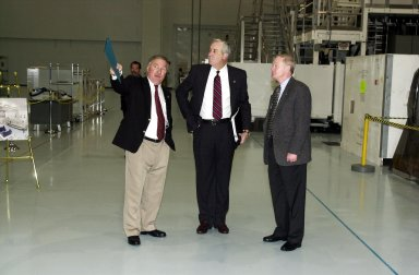 KENNEDY SPACE CENTER, Fla. - In the Space Station Processing Facility, Director of International Space Station/Payload Processing Tip Talone (left) informs the new NASA Administrator Sean O'Keefe (center) about the elements of the Space Station. At right is Center Director Roy Bridges Jr. The administrator was at KSC on an agencywide familiarization tour of NASA field centers. He was nominated for the position as administrator in November 2001 by President George W. Bush. He was sworn in Dec. 21 as the agency's 10th chief
