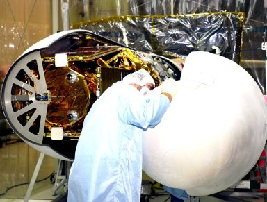 VANDENBERG AFB, CALIF. -- A worker helps guide the second half of the encapsulation around the High Energy Solar Spectroscopic Imager (HESSI) atop the Pegasus XL rocket before its transport to Florida. The Pegasus is the vehicle that will launch HESSI on its primary mission to explore the basic physics of particle acceleration and energy release in solar flares. The launch of PegasusXL/HESSI is scheduled for Feb. 5, 2002, from beneath an Orbital Sciences Corp. L-1011 aircraft over the Atlantic Ocean