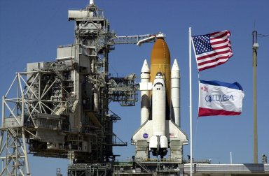 KENNEDY SPACE CENTER, FLA. -- The Rotating Service Structure is rolled back from Space Shuttle Columbia in preparation for launch Feb. 28, 2002, at 6:48 a.m. EST (11:48 GMT) on mission STS-109. Flags of the U.S. and the orbiter (foreground) illustrate the brisk winds blowing at Launch Complex 39A. In the photo is seen the Orbiter Access Arm stretched to Columbia's cockpit. A Hubble Servicing Mission, the goal of STS-109 is to replace Solar Array 2 with Solar Array 3, replace the Power Control Unit, remove the Faint Object Camera and install the ACS, install the Near Infrared Camera and Multi-Object Spectrometer (NICMOS) Cooling System, and install New Outer Blanket Layer insulation.