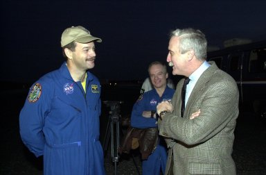 KENNEDY SPACE CENTER, FLA. -- After landing Columbia on its return from mission STS-109 - servicing the Hubble Space Telescope -- Commander Scott Altman (left) talks with NASA Administrator Sean O'Keefe. In the background is astronaut Charlie Precourt, who flew weather reconnaissance for the landing. Columbia returned to Earth the crew of seven after a mission elapsed time of 10 days, 22 hours, 11 minutes. Wheel stop occurred on orbit 165 at 4:33:09 a.m. EST. Main gear touchdown occurred at 4:31:52 a.m. and nose wheel touchdown an 4:32:02. It was the 58th landing at KSC out of 108 missions in the history of the Shuttle program