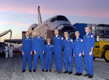KENNEDY SPACE CENTER, FLA. -- Before orbiter Columbia is towed from the Shuttle Landing Facility to the Orbiter Processing Facility, the STS-109 crew poses for photo. From left to right are Mission Specialists James Newman, Michael Massimino and Nancy Jane Currie; Commander Scott Altman; Pilot Duane Carey; Payload Commander John Grunsfeld; and Mission Specialist Richard Linnehan. The crew returned to Earth after a successful 11-day mission servicing the Hubble Space Telescope. Wheel stop occurred on orbit 165 at 4:33:09 a.m. EST. Main gear touchdown occurred at 4:31:52 a.m. and nose wheel touchdown at 4:32:02. Rollout time was 1 minute, 17 seconds. This was the 58th landing at KSC out of 108 missions in the history of the Shuttle program