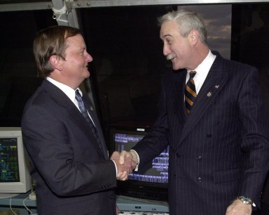 KENNEDY SPACE CENTER, Fla. - In the firing room, NASA Administrator Sean O'Keefe (right) congratulates Launch Director Mike Leinbach for the successful on-time launch of Space Shuttle Columbia. Liftoff occurred at 6:22:02:08 a.m. EST (11:22:02:08 GMT). Columbia is on its 27th flight and the 108th flight of the Shuttle Program. The goal of the mission is the maintenance and upgrade of the Hubble Space Telescope, to be carried out in five spacewalks. The crew of STS-109 comprises Commander Scott D. Altman, Pilot Duane G. Carey, Payload Commander John M. Grunsfeld, and Mission Specialists Nancy Jane Currie, Richard M. Linnehan, James H. Newman and Michael J. Massimino. After an 11-day mission, Columbia is expected to return to Kennedy March 12 about 4:35 a.m. EST (09:35 GMT)