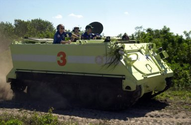 KENNEDY SPACE CENTER, FLA. -- With STS-110 Mission Specialists Jerry Ross (far left) and Steven Smith (third from left) on board, Commander Michael Bloomfield scatters dust as he practices driving the M-113 armored personnel carrier. The driving is part of Terminal Countdown Demonstration Test activities, which include emergency egress training and a simulated launch countdown. The TCDT is held at KSC prior to each Space Shuttle flight. Scheduled for launch April 4, the 11-day mission will feature Shuttle Atlantis docking with the International Space Station (ISS) and delivering the S0 truss, the centerpiece-segment of the primary truss structure that will eventually extend over 300 feet