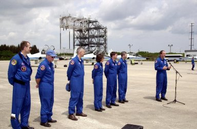 """KENNEDY SPACE CENTER, FLA. -- After landing at the KSC Shuttle Landing Facility to prepare for launch April 4, the STS-110 crew pauses for a photo and a few words to the media. Standing left to right are Mission Specialists Steven Smith, Jerry Ross, Lee Morin, Ellen Ocho and Rex Walheim; Pilot Stephen Frick; and Commander Michael Bloomfield at the microphone. Mission STS-110 is the 13th assembly flight to the International Space Station. During four planned spacewalks, crew members will install the S0 Integrated Truss Structure (ITS), centerpiece of the orbiting International Space Station (ISS), at the center of the 10-truss, girderlike structure that will ultimately extend the length of a football field on the ISS. The S0 truss will be attached to the U.S. Lab, """"Destiny,"""" on the 11-day mission"""