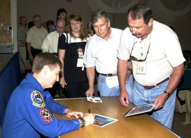 KENNEDY SPACE CENTER, FLA. -- Astronaut Frank Culbertson (left) autographs photos for KSC employees following his presentation on his experiences as commander of Expedition 3 aboard the International Space Station. Culbertson began his stay on ISS in August 2001 and returned Dec. 17 aboard Endeavour after mission STS-108.