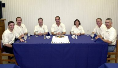 """KENNEDY SPACE CENTER, FLA. -- The STS-110 crew relaxes at the traditional crew meal before getting ready for launch later in the day. Seated, from left, are Mission Specialits Rex J. Walheim and Steven L. Smith; Pilot Stephen N. Frick; Commander Michael J. Bloomfield; and Mission Specialists Ellen Ochoa, Jerry L. Ross and Lee M.E. Morin. The cake on the table is also traditional, featuring the mission patch. STS-110 is the 13th assembly flight to the International Space Station, carrying the S0 Integrated Truss Structure and Mobile Transporter (MT). On the 11-day mission, the mission features four spacewalks to attach the S0 truss, which will become the backbone of the Space Station, to the U.S. Lab, """"Destiny."""" The MT, a space """"railcar,"""" is attached to the truss segment and will make its debut run during the flight. Among the seven astronauts, Walheim and Frick are making their first Shuttle flight; Ross is making a record-breaking seventh flight. Launch is scheduled for 4:40 p.m. EDT April 8"""