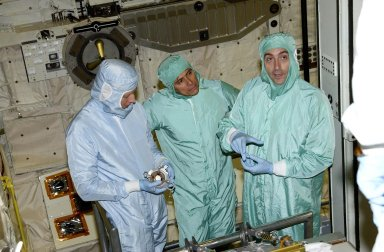 """KENNEDY SPACE CENTER, FLA. -- In the Orbiter Processing Facility, STS-111 Mission Specialists Franklin Chang-Diaz (center) and Phillippe Perrin (right) check equipment with a trainer (left) in orbiter Endeavour. Perrin is with the French Space Agency (CNES). Perrin and Chang-Diaz, with other crew members, are taking part in a Crew Equipment Interface Test in preparation for launch. Mission STS-111 will carry to the International Space Station the Multipurpose Logistics Module (MPLM), filled with experiment racks and three stowage and resupply racks, and the Mobile Base System (MBS), which will attach to the Mobile Transporter and complete the Canadian Mobile Servicing System, or MSS. The Station's mechanical arm will then have the capability to """"inchworm"""" from the U.S. Lab to the MSS and travel along the truss to work sites on the Station. Launch of Endeavour on mission STS-111 is scheduled for May 30, 2002"""