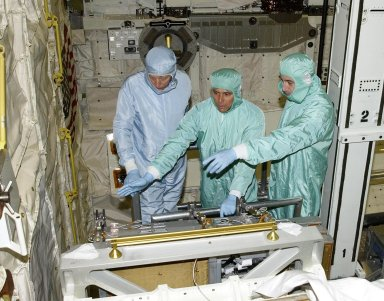 """KENNEDY SPACE CENTER, FLA. - In the Orbiter Processing Facility, STS-111 Mission Specialists Franklin Chang-Diaz (center) and Phillippe Perrin (right) look over equipment with a trainer (left) in orbiter Endeavour. Perrin is with the French Space Agency (CNES). Perrin and Chang-Diaz, with other crew members, are taking part in a Crew Equipment Interface Test in preparation for launch. Mission STS-111 will carry to the International Space Station the Multipurpose Logistics Module (MPLM), filled with experiment racks and three stowage and resupply racks, and the Mobile Base System (MBS), which will attach to the Mobile Transporter and complete the Canadian Mobile Servicing System, or MSS. The Station's mechanical arm will then have the capability to """"inchworm"""" from the U.S. Lab to the MSS and travel along the truss to work sites on the Station. Launch of Endeavour on mission STS-111 is scheduled for May 30, 2002"""