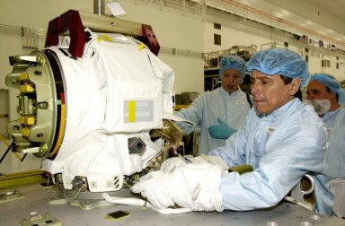"""KENNEDY SPACE CENTER, FLA. - STS-111 Mission Specialist Franklin Chang-Diaz (right) practices a maneuver on the replacement pitch roll joint for the SSRMS (Canadarm 2). The joint will be installed during the mission to the International Space Station. Part of the payload on mission STS-111 is the Mobile Base System (MBS), which will be installed on the Mobile Transporter to complete the Canadian Mobile Servicing System, or MSS. The mechanical arm will then have the capability to """"inchworm"""" from the U.S. Lab Destiny to the MSS and travel along the truss to work sites. STS-111 is the second utilization flight (UF-2) to the Space Station and will also carry the Expedition 5 crew to replace Expedition 4. Launch is scheduled for May 30, 2002"""