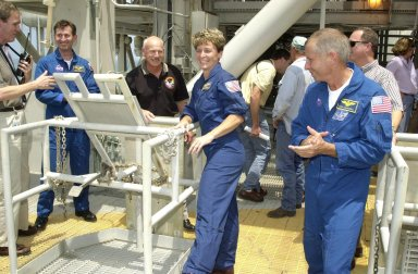 """KENNEDY SPACE CENTER, FLA. - Members of the STS-111 and Expedition 5 crews take part in emergency egress training on Launch Pad 39A. From Expedition 5 are, left, in the blue suit, Sergei Treschev and, center, Peggy Whitson. At right is Mission Commander Kenneth Cockrell. The training is part of Terminal Countdown Demonstration Test activities for the two crews. The TCDT also includes a simulated launch countdown. Mission STS-111 is known as Utilization Flight 2, carrying supplies and equipment in the Multi-Purpose Logistics Module Leonardo to the International Space Station. The payload also includes the Mobile Base System, which will be installed on the Mobile Transporter to complete the Canadian Mobile Servicing System, or MSS, and a replacement wrist/roll joint for Canadarm 2. The mechanical arm will then have the capability to """"inchworm"""" from the U.S. Lab Destiny to the MSS and travel along the truss to work sites. Expedition 5 will travel to the Station on Endeavour as the replacement crew for Expedition 4, who will return to Earth aboard the orbiter. Launch is scheduled for May 30, 2002"""