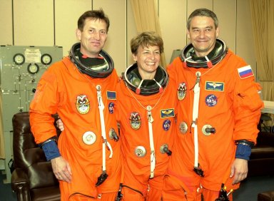 """KENNEDY SPACE CENTER, FLA. - The Expedition 5 crew pauses during suitup before going to the pad for a simulated launch countdown, part of Terminal Countdown Demonstration Test activities. From left are cosmonaut Sergei Treschev, astronaut Peggy Whitson and Commander Valeri Korzun. . Expedition 5 will travel to the International Space Station on mission STS-111 as the replacement crew for Expedition 4, who will return to Earth aboard Endeavour. Mission STS-111 is known as Utilization Flight 2, carrying supplies and equipment in the Multi-Purpose Logistics Module Leonardo to the Station. The payload also includes the Mobile Base System, which will be installed on the Mobile Transporter to complete the Canadian Mobile Servicing System, or MSS, and a replacement wrist/roll joint for Canadarm 2. The mechanical arm will then have the capability to """"inchworm"""" from the U.S. Lab Destiny to the MSS and travel along the truss to work sites. Launch is scheduled for May 30, 2002"""