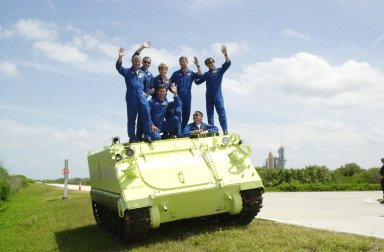 KENNEDY SPACE CENTER, FLA. -- Gathered on top of the M-113 armored personnel carrier they practiced driving during emergency egress training at the pad , the STS-11 and Expedition 5 crews wave at the camera. Standing, left to right, are Mission Commander Kenneth Cockrell, Mission Specialist Philippe Perrin, Expedition 5 member Peggy Whitson, Pilot Paul Lockhart and Mission Specialist Franklin Chang-Diaz; in front are Expedition 5 members Sergei Treschev (left) and Commander Valeri Korzun (right). The crews are taking part in Terminal Countdown Demonstration Test activities at KSC, which include a simulated launch countdown. Expedition 5 will travel to the International Space Station on mission STS-111 as the replacement crew for Expedition 4, who will return to Earth aboard Endeavour. Known as Utilization Flight -2, the mission includes attaching a Canadian-built mobile base system to the International Space Station that will enable the Canadarm2 robotic arm to move along a railway on the Station's truss to build and maintain the outpost. The crew will also replace a faulty wrist/roll joint on the Canadarm2 as well as unload almost three tons of experiments and supplies from the Italian-built Multi-Purpose Logistics Module Leonardo. Launch of Space Shuttle Endeavour on mission STS-111 is scheduled for May 30, 2002