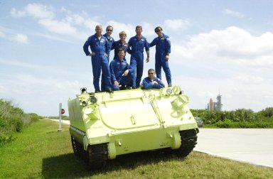 KENNEDY SPACE CENTER, FLA. - The STS-111 and Expedition 5 crews pose on top of the M-113 armored personnel carrier they practiced driving during emergency egress training at the pad. Standing, left to right, are Mission Commander Kenneth Cockrell, Mission Specialist Philippe Perrin, Expedition 5 member Peggy Whitson, Pilot Paul Lockhart and Mission Specialist Franklin Chang-Diaz; in front are Expedition 5 members Sergei Treschev (left) and Commander Valeri Korzun (right). The crews are taking part in Terminal Countdown Demonstration Test activities at KSC, which include a simulated launch countdown. Expedition 5 will travel to the International Space Station on mission STS-111 as the replacement crew for Expedition 4, who will return to Earth aboard Endeavour. Known as Utilization Flight -2, the mission includes attaching a Canadian-built mobile base system to the International Space Station that will enable the Canadarm2 robotic arm to move along a railway on the Station's truss to build and maintain the outpost. The crew will also replace a faulty wrist/roll joint on the Canadarm2 as well as unload almost three tons of experiments and supplies from the Italian-built Multi-Purpose Logistics Module Leonardo. Launch of Space Shuttle Endeavour on mission STS-111 is scheduled for May 30, 2002