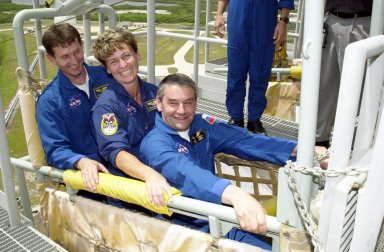 """KENNEDY SPACE CENTER, FLA. -- Expedition 5 crew members test the slidewire basket on Launch Pad 39A as part of emergency egress training at the pad. From left are Sergei Treschev, Peggy Whitson and Commander Valeri Korzun. The training is part of Terminal Countdown Demonstration Test activities for Expedition 5 and the STS-111 crew. The TCDT also includes a simulated launch countdown. Mission STS-111 is known as Utilization Flight 2, carrying supplies and equipment in the Multi-Purpose Logistics Module Leonardo to the International Space Station. The payload also includes the Mobile Base System, which will be installed on the Mobile Transporter to complete the Canadian Mobile Servicing System, or MSS, and a replacement wrist/roll joint for Canadarm 2. The mechanical arm will then have the capability to """"inchworm"""" from the U.S. Lab Destiny to the MSS and travel along the truss to work sites. Expedition 5 will travel to the Station on Endeavour as the replacement crew for Expedition 4, who will return to Earth aboard the orbiter. Launch is scheduled for May 30, 2002"""