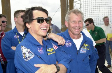 """KENNEDY SPACE CENTER, FLA. - During emergency egress training at the pad, STS-111 Mission Specialist Franklin Chang-Diaz (left, foreground) and Commander Kenneth Cockrell share a lighthearted moment. Behind Chang-Diaz is Expedition 5 Commander Valeri Korzun. The training is part of Terminal Countdown Demonstration Test activities, which also include a simulated launch countdown. Mission STS-111 is known as Utilization Flight 2, carrying supplies and equipment in the Multi-Purpose Logistics Module Leonardo to the International Space Station. The payload also includes the Mobile Base System, which will be installed on the Mobile Transporter to complete the Canadian Mobile Servicing System, or MSS, and a replacement wrist/roll joint for Canadarm 2. The mechanical arm will then have the capability to """"inchworm"""" from the U.S. Lab Destiny to the MSS and travel along the truss to work sites. Expedition 5 will travel to the Station on Endeavour as the replacement crew for Expedition 4, who will return to Earth aboard the orbiter. Launch is scheduled for May 30, 2002"""