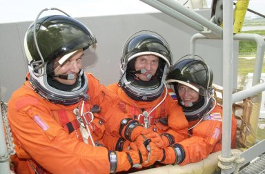 """KENNEDY SPACE CENTER, FLA. - The Expedition 5 crew - Commander Valeri Korzun (left), Sergei Treschev (center) and Peggy Whitson (right) - are in the slidewire basket and ready to exit the Fixed Service Structure on Launch Pad 39A. They and the STS-111 crew are taking part in Terminal Countdown Demonstration Test activities, which include emergency egress training and a simulated launch countdown. Mission STS-111 is Utilization Flight 2, carrying equipment and supplies in the Multi-Purpose Logistics Module Leonardo to the International Space Station, plus the Mobile Base System (MBA) and an Orbital Replacement Unit. The MBS will be installed on the Mobile Transporter to complete the Canadian Mobile Servicing System, or MSS, enabling Canadarm 2 to """"inchworm"""" from the U.S. Lab Destiny to the MSS and travel along the truss to work sites. The Expedition 5 crew is traveling on Endeavour to replace the Expedition 4 crew on the Station. Launch of Endeavour is scheduled for May 30, 2002"""