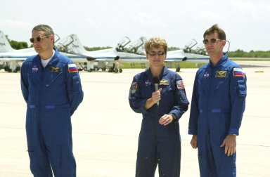 """KENNEDY SPACE CENTER, FLA. -- Astronaut Peggy Whitson (center), along with other Expedition 5 members Commander Valeri Korzun (left) and cosmonaut Sergei Treschev (right), speaks to the media before departing KSC after completing Terminal Countdown Demonstration Test activities that include emergency egress training and a simulated launch countdown. Expedition 5 will travel to the International Space Station on mission STS-111 as the replacement crew for Expedition 4, who will return to Earth aboard the orbiter. Mission STS-111 is known as Utilization Flight 2, carrying supplies and equipment in the Multi-Purpose Logistics Module Leonardo to the International Space Station. The payload also includes the Mobile Base System, which will be installed on the Mobile Transporter to complete the Canadian Mobile Servicing System, or MSS, and a replacement wrist/roll joint for Canadarm 2. The mechanical arm will then have the capability to """"inchworm"""" from the U.S. Lab Destiny to the MSS and travel along the truss to work sites. Launch is scheduled for May 30, 2002"""