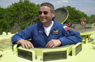 KENNEDY SPACE CENTER, FLA. - During Terminal Countdown Demonstration Test activities at KSC, Expedition 5 Commander Valeri Korzun smiles for a photo before climbing inside the M-113 armored personnel carrier, used for emergency egress training at the pad. Passengers in the vehicle are (left) astronaut Tracy Caldwell, a mission specialist candidate currently assigned to the Astronaut Office Space Station Operations Branch, and Expedition 5 member Peggy Whitson. Expedition 5 will travel to the International Space Station on mission STS-111 as the replacement crew for Expedition 4, who will return to Earth aboard Endeavour. The TCDT also includes a simulated launch countdown Known as Utilization Flight -2, the mission includes attaching a Canadian-built mobile base system to the International Space Station that will enable the Canadarm2 robotic arm to move along a railway on the Station's truss to build and maintain the outpost. The crew will also replace a faulty wrist/roll joint on the Canadarm2 as well as unload almost three tons of experiments and supplies from the Italian-built Multi-Purpose Logistics Module Leonardo. Launch of Space Shuttle Endeavour on mission STS-111 is scheduled for May 30, 2002