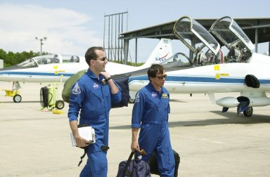 """KENNEDY SPACE CENTER, FLA. -- STS-111 Mission Specialists Philippe Perrin (left) and Franklin Chang-Diaz (right) carry their gear to the waiting T-38 jet aircraft for their return to Houston. The STS-111 and Expedition 5 crews have completed Terminal Countdown Demonstration Test activities that include emergency egress training and a simulated launch countdown. Expedition 5 will travel to the International Space Station on mission STS-111 as the replacement crew for Expedition 4, who will return to Earth aboard the orbiter. Mission STS-111 is known as Utilization Flight 2, carrying supplies and equipment in the Multi-Purpose Logistics Module Leonardo to the International Space Station. The payload also includes the Mobile Base System, which will be installed on the Mobile Transporter to complete the Canadian Mobile Servicing System, or MSS, and a replacement wrist/roll joint for Canadarm 2. The mechanical arm will then have the capability to """"inchworm"""" from the U.S. Lab Destiny to the MSS and travel along the truss to work sites. Launch is scheduled for May 30, 2002"""