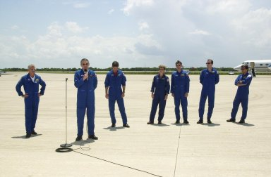 """KENNEDY SPACE CENTER, FLA. -- Expedition 5 Commander Valeri Korzun (with microphone) speaks to the media before leaving KSC. Behind him (left to right) are STS-111 Commander Kenneth Cockrell and Pilot Paul Lockhart; astronaut Peggy Whitson and cosmonaut Sergei Treschev; Mission Specialists Philippe Perrin and Franklin Chang-Diaz. Korzun and Treschev are with the Russian Space Agency; Perrin is with the French Space Agency. They have been taking part in Terminal Countdown Demonstration Test activities that include emergency egress training and a simulated launch countdown. Expedition 5 will travel to the International Space Station on mission STS-111 as the replacement crew for Expedition 4, who will return to Earth aboard the orbiter. Mission STS-111 is known as Utilization Flight 2, carrying supplies and equipment in the Multi-Purpose Logistics Module Leonardo to the International Space Station. The payload also includes the Mobile Base System, which will be installed on the Mobile Transporter to complete the Canadian Mobile Servicing System, or MSS, and a replacement wrist/roll joint for Canadarm 2. The mechanical arm will then have the capability to """"inchworm"""" from the U.S. Lab Destiny to the MSS and travel along the truss to work sites. Launch is scheduled for May 30, 2002"""