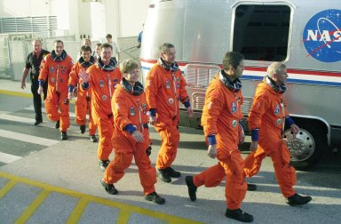 """KENNEDY SPACE CENTER, FLA. -- The STS-111 crew and Expedition 5 walk eagerly to the Astrovan that will take them to Launch Pad 39A for a simulated countdown. From left are Mission Specialists Philippe Perrin and Franklin Chang-Diaz; the Expedition 5 crew, Sergei Treschev, Peggy Whitson and Valeri Korzun; Pilot Paul Lockhart; and Commander Kenneth Cockrell. The simulation is part of STS-111 Terminal Countdown Demonstration Test activities for the crew and Expedition 5. The payload on the mission to the International Space Station includes the Mobile Base System (MBS), an Orbital Replacement Unit and Multi-Purpose Logistics Module Leonardo. The MBS will be installed on the Mobile Transporter to complete the Canadian Mobile Servicing System, or MSS, enabling Canadarm 2 to """"inchworm"""" from the U.S. Lab Destiny to the MSS and travel along the truss to work sites. The Expedition 5 crew is traveling on Endeavour to replace the Expedition 4 crew on the Station. Launch of Endeavour is scheduled for May 30, 2002"""