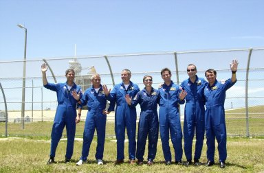 """KENNEDY SPACE CENTER, FLA. -- At Launch Pad 39-A, the STS-111 and Expedition Five crews take time out from a tour of the pad with their friends and family to pose for a group portrait. From left, they are STS-111 Pilot Paul Lockhart, STS-111 Commander Kenneth Cockrell, Expedition Five Commander Valeri Korzun (RSA), Expedition Five astronaut Peggy Whitson, Expedition Five cosmonaut Sergei Treschev (RSA), and STS-111 Mission Specialists Philippe Perrin (CNES) and Franklin Chang-Diaz. Expedition Five is traveling to the International Space Station on Space Shuttle Endeavour as the replacement crew for Expedition Four, who will return to Earth aboard the orbiter. Known as Utilization Flight 2, STS-111 is carrying supplies and equipment to the Station. The payload includes the Multi-Purpose Logistics Module Leonardo, the Mobile Base System, which will be installed on the Mobile Transporter to complete the Canadian Mobile Servicing System, or MSS, and a replacement wrist/roll joint for Canadarm 2. The mechanical arm will then have the capability to """"inchworm"""" from the U.S. Lab Destiny to the MSS and travel along the truss to work sites. Launch is scheduled for May 30, 2002"""