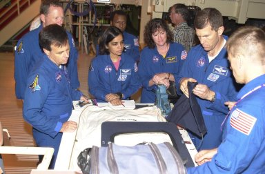 """KENNEDY SPACE CENTER, FLA. -- During Crew Equipment Interface Test activities, the STS-107 crew looks at flight equipment in the Orbiter Processing Facility. Seen left to right are Payload Specialist Ilan Ramon, who is with the Israeli Space Agency, Mission Specialists David Brown and Kalpana Chawla, Commander Rick Husband and Pilot William """"Willie"""" McCool. Behind Chawla is Payload Commander Michael Anderson. STS-107 is a research mission, with the SHI Research Double Module (SHI/RDM), also known as SPACEHAB, as the primary payload, plus the Fast Reaction Experiments Enabling Science, Technology, Applications and Research (FREESTAR) that incorporates eight high priority secondary attached shuttle experiments. STS-107 is scheduled to launch July 19, 2002"""