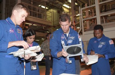 """KENNEDY SPACE CENTER, FLA. -- -- During Crew Equipment Interface Test activities, the STS-107 crew looks at flight equipment in the Orbiter Processing Facility. From left are Pilot William """"Willie"""" McCool, Mission Specialist Kalpana Chawla, Commander Rick Husband and Payload Commander Michael Anderson. STS-107 is a research mission, with the SHI Research Double Module (SHI/RDM), also known as SPACEHAB, as the primary payload, plus the Fast Reaction Experiments Enabling Science, Technology, Applications and Research (FREESTAR) that incorporates eight high priority secondary attached shuttle experiments. STS-107 is scheduled to launch July 19, 2002"""