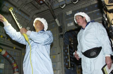 KENNEDY SPACE CENTER, FLA. - STS-107 Mission Specialists Ilan Ramon, with the Israeli Space Agency, and Laurel Clark check out equipment in the SHI Research Double Module (SHI/RDM), part of the payload on the mission. They are taking part in Crew Equipment Interface Test activities, which include equipment and payload familiarization. A research mission, STS-107 also will carry the Fast Reaction Experiments Enabling Science, Technology, Applications and Research (FREESTAR) that incorporates eight high priority secondary attached shuttle experiments. STS-107 is scheduled to launch July 19, 2002