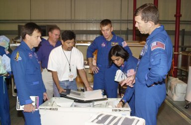 """KENNEDY SPACE CENTER, FLA. -- During Crew Equipment Interface Test activities, the STS-107 crew looks at flight equipment in the Orbiter Processing Facility. From left are Payload Specialist Ilan Ramon (with the Israeli Space Agency), Pilot William """"Willie"""" McCool (center), Mission Specialist Kalpana Chawla and Commander Rick Husband. STS-107 is a research mission, with the SHI Research Double Module (SHI/RDM), also known as SPACEHAB, as the primary payload, plus the Fast Reaction Experiments Enabling Science, Technology, Applications and Research (FREESTAR) that incorporates eight high priority secondary attached shuttle experiments. STS-107 is scheduled to launch July 19, 2002"""