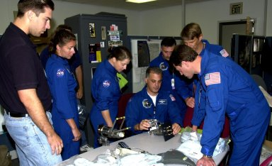 KENNEDY SPACE CENTER, FLA. - The STS-112 crew looks over equipment in the Space Station Processing Facility as part of the Crew Equipment Interface Test. From left are a technician, Mission Specialist Sandra Magnus, Pilot Pamela Melroy, Mission Specialists David Wolf (seated), Fyodor Yurchikhin and Piers Sellers, and Commander Jeffrey Ashby (in front). Yurchikhin is with the Russian Space Agency. Mission STS-112 will be ferrying the S1 ITS to the International Space Station on its scheduled Aug. 22 flight. The S1 truss is the first starboard (right-side) truss segment, whose main job is providing structural support for the orbiting research facility's radiator panels that cool the Space Station's complex power system. The S1 truss segment also will house communications systems, external experiment positions and other subsystems. The S1 truss will be attached to the S0 truss