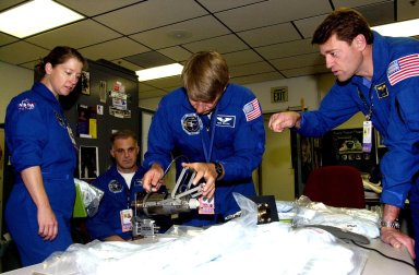 KENNEDY SPACE CENTER, FLA. -- The STS-112 crew looks over equipment in the Space Station Processing Facility as part of the Crew Equipment Interface Test. From left are Pilot Pamela Melroy, Mission Specialists David Wolf (seated) and Piers Sellers, and Commander Jeffrey Ashby. Mission STS-112 will be ferrying the S1 ITS to the International Space Station on its scheduled Aug. 22 flight. The S1 truss is the first starboard (right-side) truss segment, whose main job is providing structural support for the orbiting research facility's radiator panels that cool the Space Station's complex power system. The S1 truss segment also will house communications systems, external experiment positions and other subsystems. The S1 truss will be attached to the S0 truss