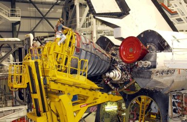 KENNEDY SPACE CENTER, FLA. -- The first Space Shuttle Main Engine (SSME) is installed on Space Shuttle Atlantis following the welding repair of the propulsion system flow liners as preparations to launch mission STS-112 continue. Sitting atop the engine is Angela DiMattia, the move director for Rocketdyne. Just behind and below her is Rocketdyne employee Brickford Lero, offering some additional guidance. Mission STS-112 is an assembly flight to the International Space Station and is targeted for launch no earlier than Sept. 28, 2002. Members of the STS-112 crew are Commander Jeffrey Ashby; Pilot Pamela Melroy; and Mission Specialists David Wolf, Piers Sellers, Sandra Magnus, and Fyodor Yurchikhin of the Russian Space Agency.