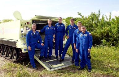 KENNEDY SPACE CENTER, Fla. - The STS-112 crew poses for a photo on the back of the M-113 armored personnel carrier they practiced driving as part of Terminal Countdown Demonstration Test activities. From left are Mission Specialist David Wolf, Pilot Pamela Melroy, Mission Specialist Sandra Magnus, Commander Jeffrey Ashby, and Mission Specialists Piers Sellers and Fyodor Yurchikhin, who is with the Russian Space Agency. Mission STS-112 aboard Space Shuttle Atlantis is scheduled to launch no earlier than Oct. 2, between 2 and 6 p.m. EDT. STS-112 is the 15th assembly mission to the International Space Station. Atlantis will be carrying the S1 Integrated Truss Structure, the first starboard truss segment. The S1 will be attached to the central truss segment, S0, during the 11-day mission.