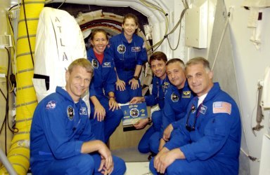 KENNEDY SPACE CENTER, FLA. -- The STS-112 crew pauses for a photo in the White Room during Terminal Countdown Demonstration Test activities. From left, clockwise, are Mission Specialists Piers Sellers and Sandra Magnus, Pilot Pamela Melroy, Commander Jeffrey Ashby and Mission Specialists Fyodor Yurchikhin and David Wolf. Ashby is holding the mission insignia. Yurchikhin is with the Russian Space Agency. Mission STS-112 aboard Space Shuttle Atlantis is scheduled to launch no earlier than Oct. 2, between 2 and 6 p.m. EDT. STS-112 is the 15th assembly mission to the International Space Station. Atlantis will be carrying the S1 Integrated Truss Structure, the first starboard truss segment, to be attached to the central truss segment, S0, and the Crew and Equipment Translation Aid (CETA) Cart A. The CETA is the first of two human-powered carts that will ride along the ISS railway, providing mobile work platforms for future spacewalking astronauts.
