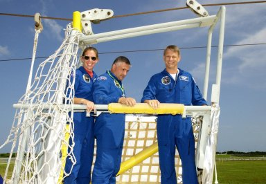 KENNEDY SPACE CENTER, FLA. -- Members of the STS-112 crew stand inside a slidewire basket, a component of the emergency egress system at the pad. From left are Mission Specialists Sandra Magnus, Fyodor Yurchikhin (with the Russian Space Agency), and Piers Sellers. The training is part of Terminal Countdown Demonstration Test activities, which include a simulated launch countdown. Mission STS-112 aboard Space Shuttle Atlantis is scheduled to launch no earlier than Oct. 2, between 2 and 6 p.m. EDT. STS-112 is the 15th assembly mission to the International Space Station. Atlantis will be carrying the S1 Integrated Truss Structure, the first starboard truss segment, to be attached to the central truss segment, S0, and the Crew and Equipment Translation Aid (CETA) Cart A. The CETA is the first of two human-powered carts that will ride along the ISS railway, providing mobile work platforms for future spacewalking astronauts.