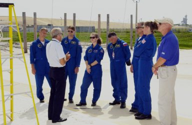 KENNEDY SPACE CENTER, FLA. -- The STS-112 crew listen to further instructions about emergency egress from the Shuttle. Standing, left to right, are Mission Specialist Piers Sellers, Commander Jeffrey Ashby, Pilot Pamela Melroy, Mission Specialists Fyodor Yurchikhin (with the Russian Space Agency), David Wolf and Sandra Magnus. The training is part of Terminal Countdown Demonstration Test activities, which include a simulated launch countdown. Mission STS-112 aboard Space Shuttle Atlantis is scheduled to launch no earlier than Oct. 2, between 2 and 6 p.m. EDT. STS-112 is the 15th assembly mission to the International Space Station. Atlantis will be carrying the S1 Integrated Truss Structure, the first starboard truss segment, to be attached to the central truss segment, S0, and the Crew and Equipment Translation Aid (CETA) Cart A. The CETA is the first of two human-powered carts that will ride along the ISS railway, providing mobile work platforms for future spacewalking astronauts.