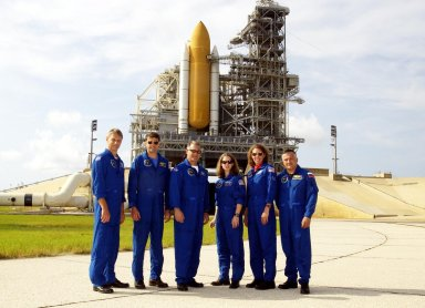 KENNEDY SPACE CENTER, FLA. -- During Terminal Countdown Demonstration Test activities, the STS-112 crew poses for a group photo near the launch pad where Space Shuttle Atlantis waits for launch. Standing left to right are Mission Specialist Piers Sellers, Commander Jeffrey Ashby, Mission Specialist David Wolf, Pilot Pamela Melroy, and Mission Specialists Sandra Magnus and Fyodor Yurchikhin, who is with the Russian Space Agency. The TCDT includes emergency egress training and a simulated launch countdown. Mission STS-112 aboard Space Shuttle Atlantis is scheduled to launch no earlier than Oct. 2, between 2 and 6 p.m. EDT. STS-112 is the 15th assembly mission to the International Space Station. Atlantis will be carrying the S1 Integrated Truss Structure, the first starboard truss segment, to be attached to the central truss segment, S0, and the Crew and Equipment Translation Aid (CETA) Cart A. The CETA is the first of two human-powered carts that will ride along the ISS railway, providing mobile work platforms for future spacewalking astronauts.
