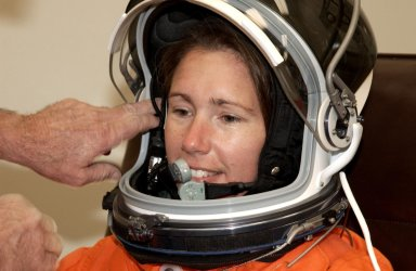 KENNEDY SPACE CENTER, Fla. - STS-112 Mission Specialist Sandra Magnus has her helmet adjusted during suit check, part of Terminal Countdown Demonstration Test activities. The TCDT also includes emergency egress training and a simulated launch countdown. The mission aboard Space Shuttle Atlantis is scheduled to launch no earlier than Oct. 2, between 2 and 6 p.m. EDT. STS-112 is the 15th assembly mission to the International Space Station. Atlantis will be carrying the S1 Integrated Truss Structure, the first starboard truss segment. The S1 will be attached to the central truss segment, S0, during the 11-day mission. Magnus will serve as one of two operators of the Canadarm2 robotic arm for S1 truss installation and during three scheduled spacewalks. STS-112 is her first Shuttle flight.