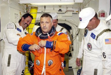 KENNEDY SPACE CENTER, FLA. -- In the White Room at Launch Pad 39B, STS-112 Mission Specialist Fyodor Yurchikhin, Ph.D., a cosmonaut with the Russian Space Agency, receives assistance with his spacesuit during a simulated launch countdown, part of Terminal Countdown Demonstration Test activities, a dress rehearsal for launch. Launch of STS-112 aboard Space Shuttle Atlantis is scheduled for Oct. 2, between 2 and 6 p.m. EDT. STS-112 is the 15th assembly mission to the International Space Station. Atlantis will be carrying the S1 Integrated Truss Structure, the first starboard truss segment, which will be attached to the central truss segment, S0, and the Crew and Equipment Translation Aid (CETA) Cart A. The CETA is the first of two human-powered carts that will ride along the ISS railway, providing mobile work platforms for future spacewalking astronauts.