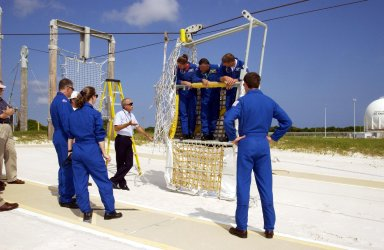 KENNEDY SPACE CENTER, FLA. -- The STS-112 crew listen to further instructions about emergency egress from the Shuttle using the slidewire basket. In the basket are Mission Specialists Sandra Magnus, Fyodor Yurchikhin (with the Russian Space Agency), and Piers Sellers. At left are Mission Specialist David Wolf and Pilot Pamela Melroy; at right is Commander Jeffrey Ashby. The training is part of Terminal Countdown Demonstration Test activities, which include a simulated launch countdown. Mission STS-112 aboard Space Shuttle Atlantis is scheduled to launch no earlier than Oct. 2, between 2 and 6 p.m. EDT. STS-112 is the 15th assembly mission to the International Space Station. Atlantis will be carrying the S1 Integrated Truss Structure, the first starboard truss segment, to be attached to the central truss segment, S0, and the Crew and Equipment Translation Aid (CETA) Cart A. The CETA is the first of two human-powered carts that will ride along the ISS railway, providing mobile work platforms for future spacewalking astronauts.
